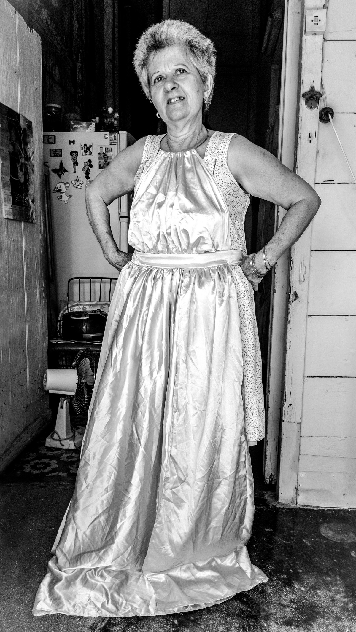 Photo noir et blanc. Une dame d'un certain âge pose à l'entrée d'une cuisine (un frigo est visible en arrière-plan). Elle a posé une robe habillée par-dessus sa robe de tous les jours.