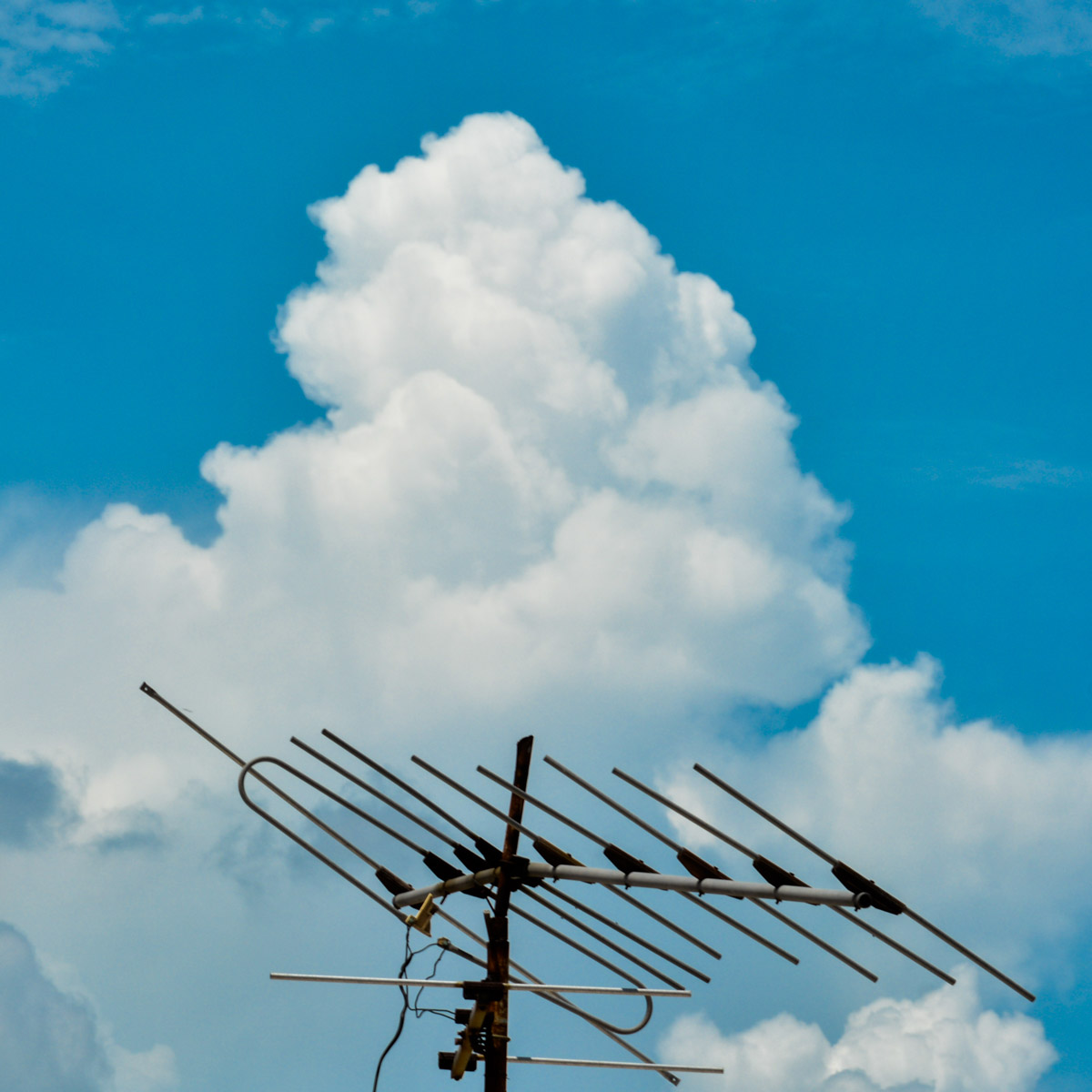 Photo couleur. Une antenne de télévision râteau se découpe sur un ciel bleu mais nuageux.