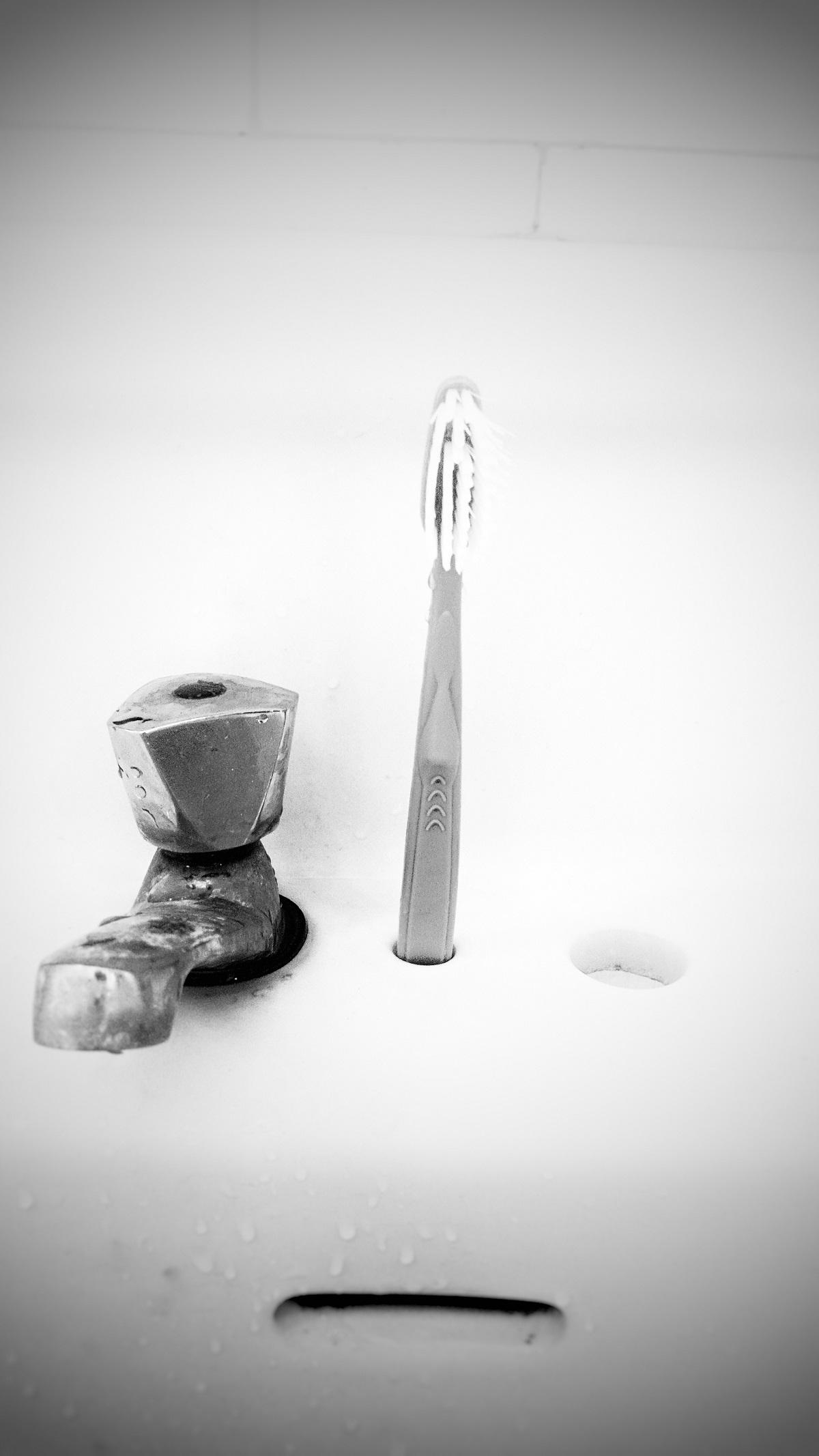 Photo noir et blanc. Elle montre un lavabo sur lequel une brosse à dent est positionnée à la verticale, à droite du robinet.