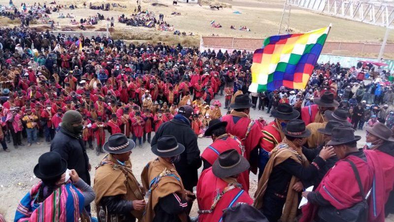 Des centaines d'Aymaras sont rassemblés, vêtus d'habits traditionnels et brandissant leur drapeau.