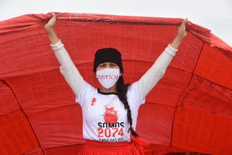"""Une femme brandit un étendard rouge sang, et porte un masque facial où est inscrit le mot """"Justice"""" en majuscules rouges."""