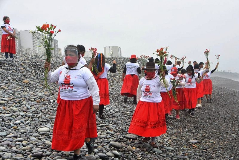 Des manifestantes ont parcouru de nombreux kilomètres pour manifester sur la plage. Elles portent des jupes rouges et des t-shirts blancs et brandissent des bouquets de roses rouges.