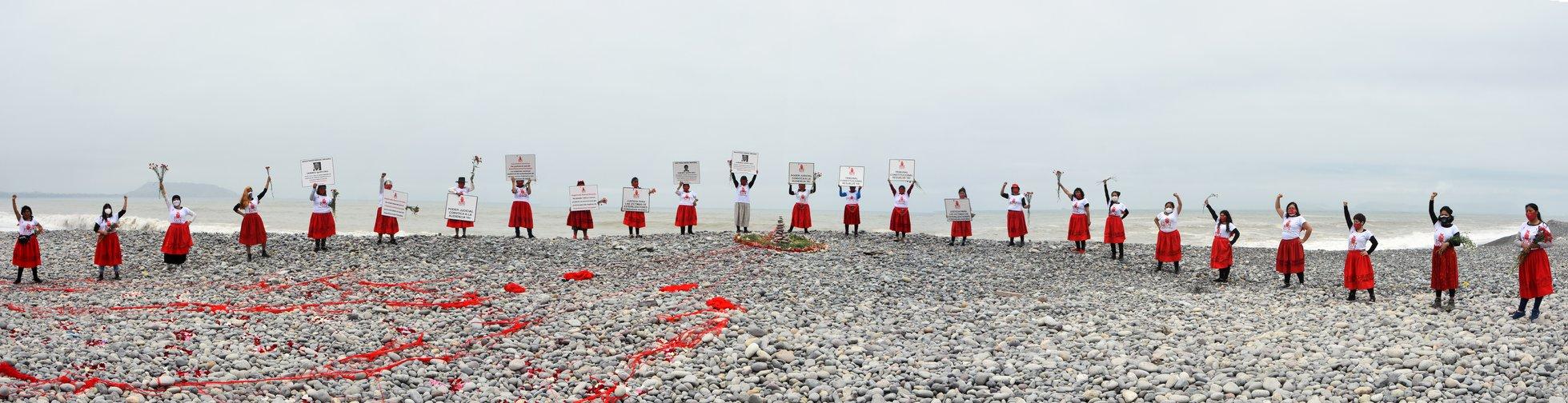 Un groupe de femmes en rouge et blanc manifeste sur une plage de Lima à l'aide de pancartes. Elles gardent leurs distances en raison de la pandémie de COVID-19.
