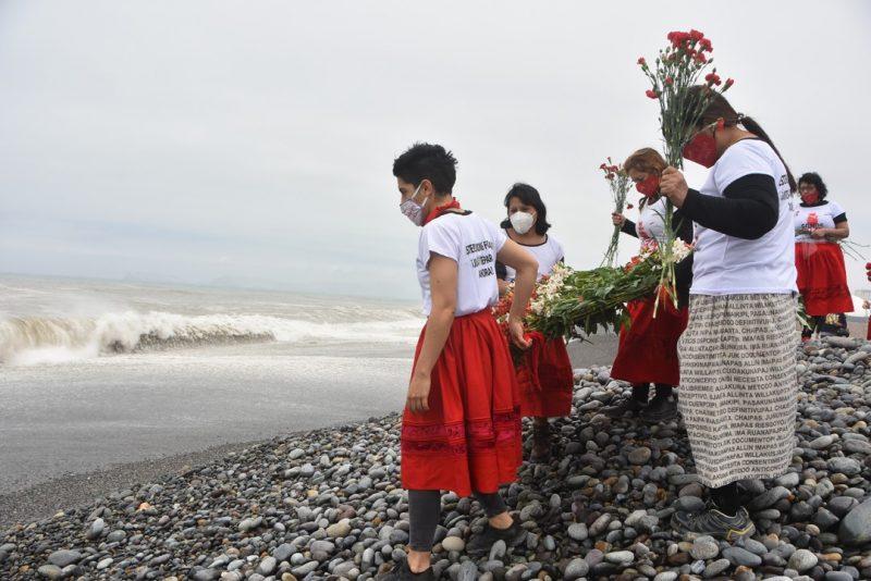 Des femmes manifestent sur la plage, portant des gerbes de fleurs. Elles portent des habits rouge et blancs, symboles de leur lutte pour les victimes de stérilisations forcées.