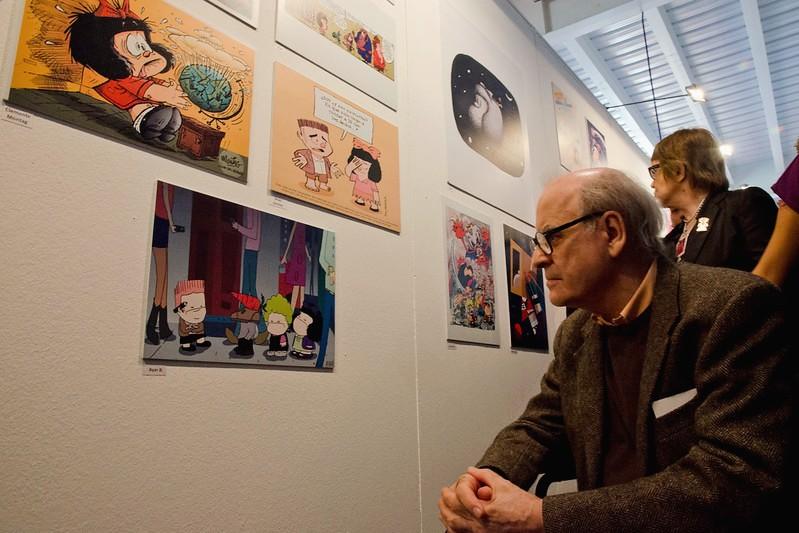 Au premier plan à droite, Quino, âgé, regarde un de ses dessins exposés au mur.