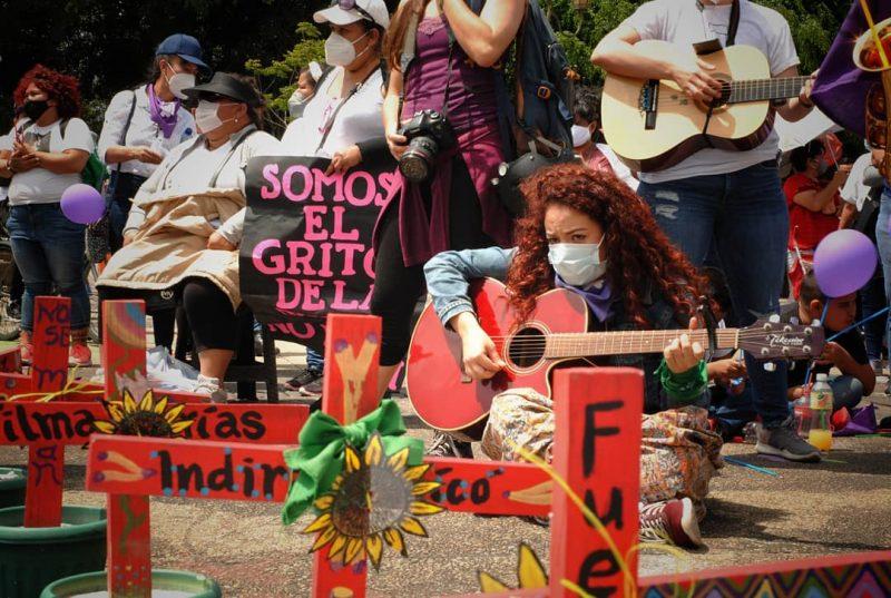 Une femme joue de la guitare en signe de protestation