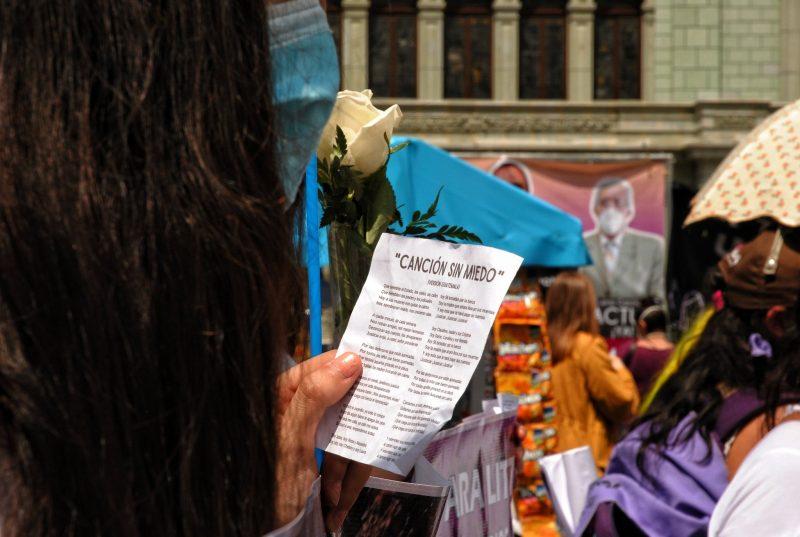 Une manifestante regarde les paroles de la chanson de Vivir Quintana