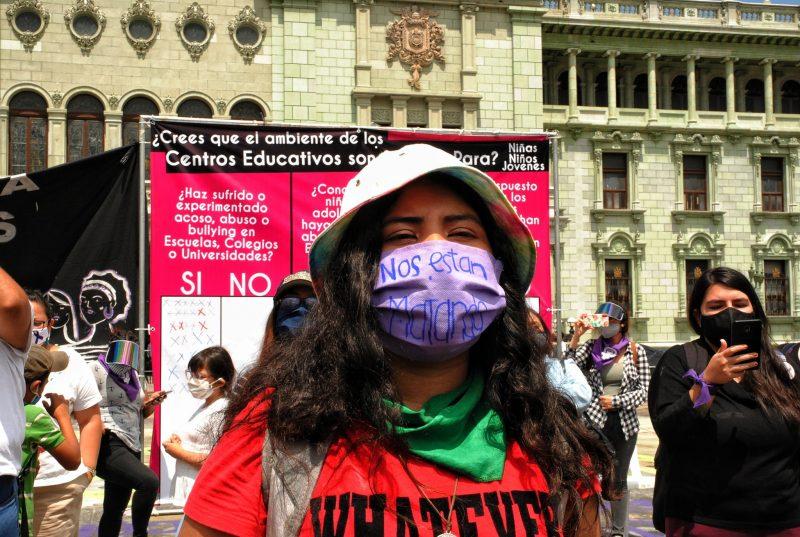 Une manifestante masquée dans la rue
