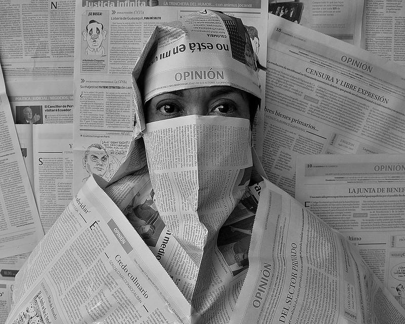 Une personne est couverte de feuilles de journal, ne laissant voir que ses yeux. Le fond est tapissé de pages de journaux, des colonnes d'opinion.