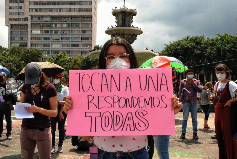 une manifestante montre sa pancarte sur laquelle figure un message solidaire