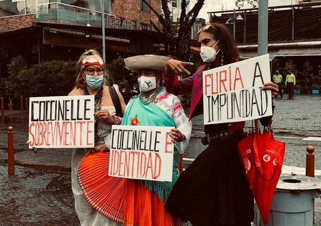 Trois femmes présentent leurs pancartes en rouge et noir lors de la marche nationale trans en Equateur.