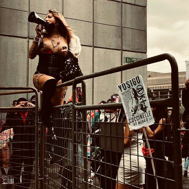 Une femme en corset noir et en longues bottes parle dans un haut-parleur, chevauchant un grillage lors de la marche nationale des personnes trans en Équateur.