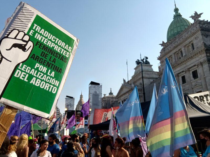 Rassemblement majoritairement de femmes dans la rue, portant des drapeaux arc-en-ciel. Au premier plan, une grande affiche portant l'entête des traductrices et des interprètes féministes d'Argentine.
