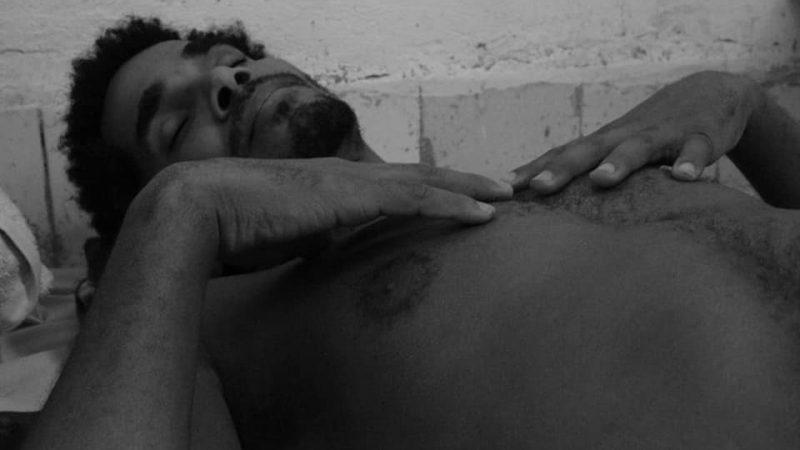 Homme en torse nu, allongé et endormi ave les mains posées sur le torse.