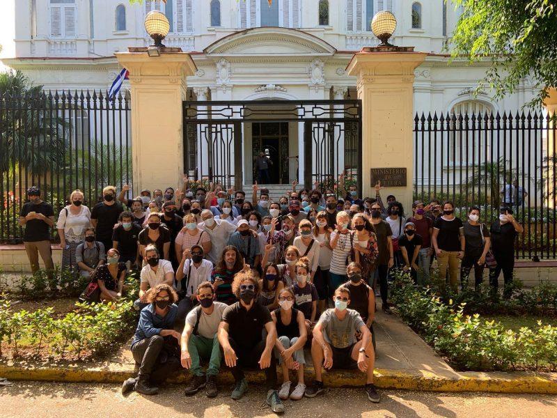 Groupe de personnes de différents âges rassemblées devant la porte d'un grand bâtiment
