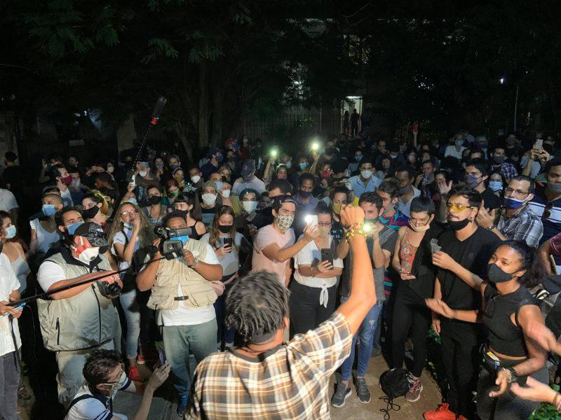 Un nombre important de jeunes rassemblés devant un homme qui fait un discours. Un photographe et un média sont aussi présents.