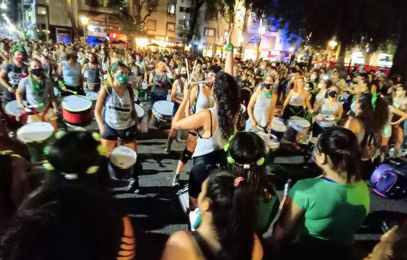 Groupe de jeunes femmes percussionnistes évoluant dans la rue.