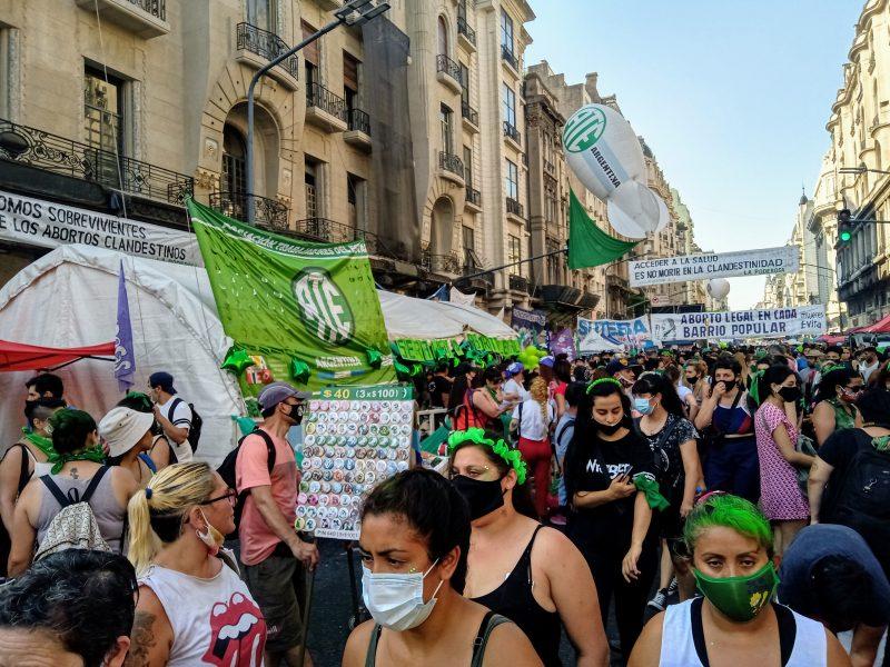 Une foule constituée de femmes majoritairement, portant des banderoles, manifestant dans la rue.