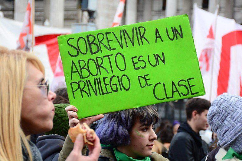 Des manifestants tiennent une pancarte avec écrit en espagnol « Survivre à un avortement est un privilège de classe »