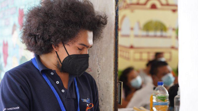 Carlos Lara, un jeune homme portant un polo est un masque de protection faciale, a la tête baissée, il semble se concentrer.