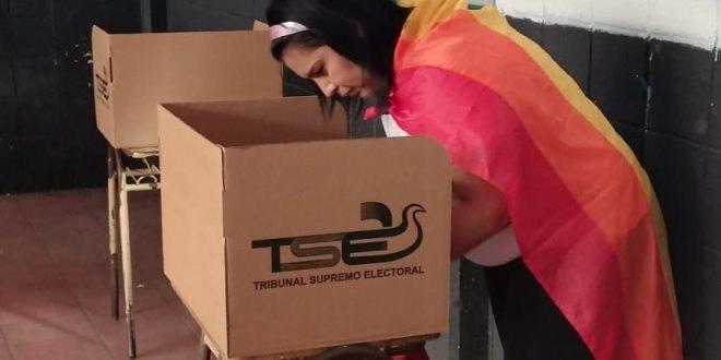 Une femme drapée dans un drapeau arc-en-ciel se penche sur un isoloir en carton marqué du logo de la Cour suprême électorale.