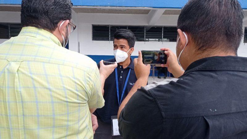 Deux journalistes, de dos, filment un membre du groupe sur leurs téléphones portables. Tous portent des masques blancs.
