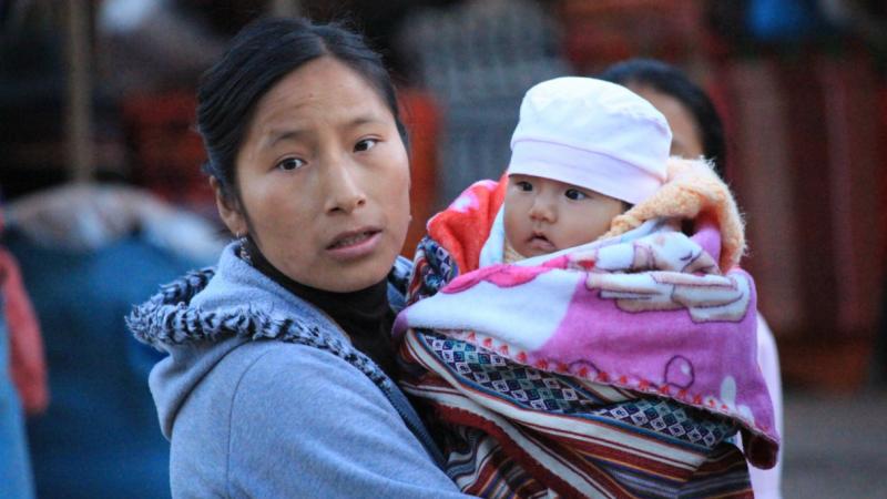 Une femme porte son bébé enroulé dans une couverture. Elle regarde l'objectif d'un air pensif.
