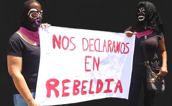 Deux femmes vêtues de noir et de rose et avec le visage caché sous des voiles et des masques Santa Muerte portent une pancarte où la phrase citée en légende est écrite en espagnol.