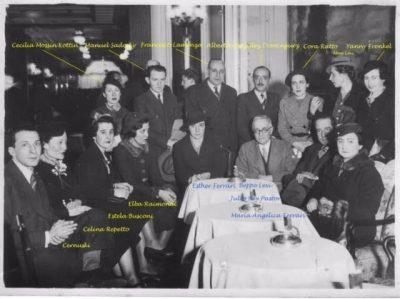 On voit sur cette photo en noir et blanc un groupe de personnes constitué de femmes et d'hommes assis autour de tables.